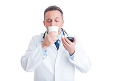 Medic or doctor smelling fresh coffee from disposable cup Stock Photo