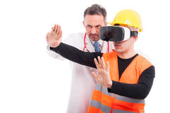 Medic helping constructor holding hands with virtual reality gla. Sses isolated on white background with copy text space Stock Image