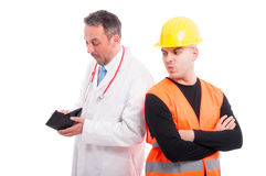 Medic looking content checking constructors wallet Royalty Free Stock Image