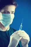 Medic looking at a syringe Royalty Free Stock Photography