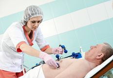 Medic nurse with patient at electrocardiogram Royalty Free Stock Image