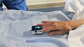 Medic and patient using finger pulse oximeter royalty free stock images