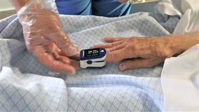 Medic and patient using finger pulse oximeter royalty free stock photography