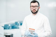 Medic portrait with test tubes indoors. Portrait of a male technician standing with test tubes in the laboratory Royalty Free Stock Images
