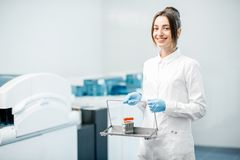 Medic portrait with test tubes indoors. Portrait of a woman technician standing with test tubes in the laboratory Stock Photo
