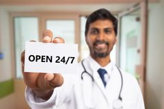 Medic presenting always open concept card. Indian male medic smiling as presenting always open concept white business card close-up with selective focus stock photos