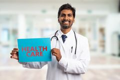 Medic showing health care paper sign. Indian male medic with friendly smile showing health care text on paper sign as hospital concept royalty free stock photos