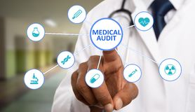 Medic touching medical audit text on display royalty free stock images