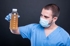 Medic wearing face mask holding not drinkable water Royalty Free Stock Images