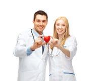 Medica cardiologistas com coração Fotografia de Stock Royalty Free