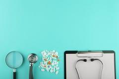 medica o local de trabalho - tabuleta médica, estetoscópio, comprimidos e lupa Imagens de Stock