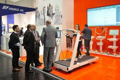 MEDICA Trade Fair, DUSSELDORF, GERMANY - NOVEMBER 2019, delegation of doctors at a medical exhibition, treadmill girl