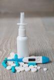 Medicación azul y blanca, espray nasal, píldoras, vitaminas, cápsulas, termómetro en fondo de madera gris Todos para la gripe Cop Foto de archivo libre de regalías