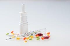 Medicación colorida, espray nasal, píldoras, vitaminas, cápsulas, termómetro Foto de archivo libre de regalías