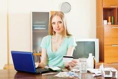 Medicación de compra de la muchacha de pelo largo rubia en farmacia en línea Imagenes de archivo
