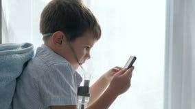 Medicación de la inhalación, muchacho en máscara de un inhalador con el teléfono celular en las manos almacen de metraje de vídeo