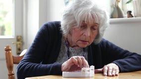 Medicación de organización de la mujer mayor en dispensador de la píldora almacen de video