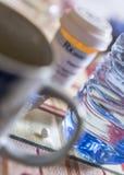 Medicaci?n durante el desayuno, c?psulas al lado de un vaso de agua foto de archivo libre de regalías