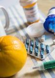 Medicación durante el desayuno, cápsulas al lado de una naranja imagenes de archivo