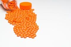 Medicación, píldoras que se derraman hacia fuera sobre una superficie blanca Fotografía de archivo