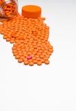 Medicación, píldoras que se derraman hacia fuera sobre una superficie blanca Fotos de archivo libres de regalías