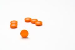 Medicación, píldoras que se derraman hacia fuera sobre una superficie blanca Fotos de archivo