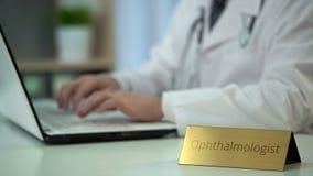 Medicación que prescribe del oftalmólogo de sexo masculino en línea, mecanografiando en el ordenador portátil metrajes