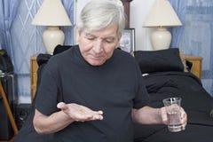 Medicación que toma mayor con agua Fotografía de archivo libre de regalías