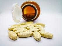 Medicación y concepto de la atención sanitaria Muchas tabletas amarillas ovales de m imagen de archivo libre de regalías