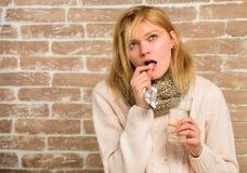 Medicaciones de la toma para reducir fiebre La mujer despeinó el agua de cristal del control de la bufanda del pelo y hace tablet imagen de archivo libre de regalías