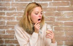 Medicaciones de la toma para reducir fiebre Remedios del dolor de cabeza y de la fiebre La mujer despeinó el agua y las tabletas  fotografía de archivo