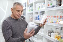 Medicaciones maduras de la compra del hombre en la droguería imagenes de archivo