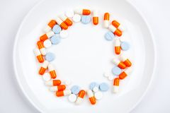 Medicaciones y píldoras en una placa de cerámica blanca en un fondo blanco fotos de archivo libres de regalías