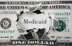 Medicaid costs. Hole torn in a dollar bill with medicaid text Stock Photos