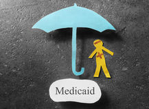 Medicaid healthcare concept. Bandaged paper man under umbrella with Medicaid message Royalty Free Stock Photography