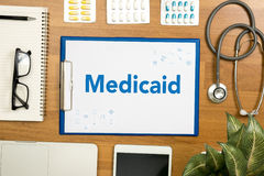 Medicaid. Professional doctor use computer and medical equipment all around, desktop top view Stock Images