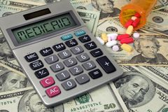 Medicaid text sign on calculator with pills and money. Medicaid text calculatoron American paper money with pills and orange prescription bottle Royalty Free Stock Image