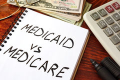 Medicaid vs Medicare written in a note. Health insurance concept Stock Photo