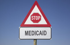 Medicaid warning. Red warning triangle with a stop sign and the word medicaid, political and social concept for us health care Stock Photography