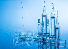 Medical ampoules and syringe on blue water background with splash and drops Royalty Free Stock Photography