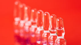 Medical ampules on a red background, selective focus. Royalty Free Stock Image