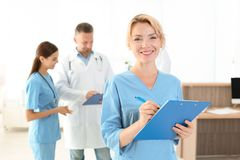 Medical assistant with colleagues in clinic. Health care service stock photo