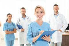 Medical assistant with colleagues in clinic. Health care service royalty free stock image