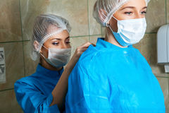 Medical assistant helps her preparing for surgery Royalty Free Stock Images