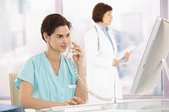Medical assistant on phone, using computer