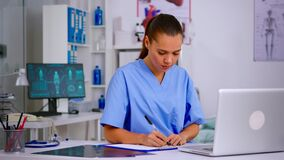 Medical assistant typing on laptop and taking notes on clipboard