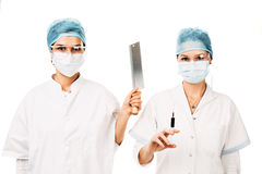 Medical assistants. Two women with protection glasses , masks and white robe holding a syringe and a cleaver - isolated on white royalty free stock image