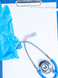 Medical background with clipboard. On the clipboard are: stethoscope, syringe and gloves Stock Images