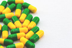 A medical background image consisting of yellow and green pills. Next to a white background Royalty Free Stock Photos