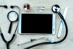 Medical background. Tablet pc with medical objects on a desk as a metaphor for electronic diagnostic or healthcare mobile apps. Medical background stock photos